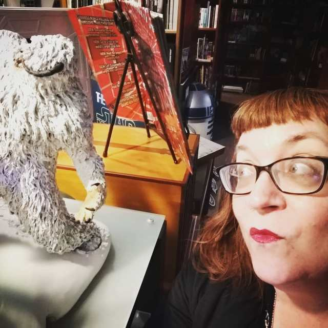 Pictured: Melissa Hillman, a redhead with short bangs, black-framed glasses, and red lipstick, gazes up and to the left at a small statue of a wampa, a creature from Star Wars.
